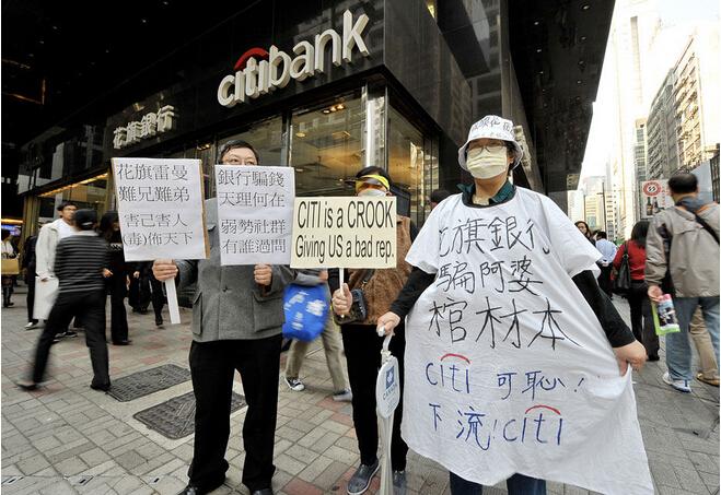 """美国的次贷危机波及到中国香港和台湾后,演变出了""""有毒债权""""的问题,引发了很多社会争论。所谓""""迷你债""""就是那些组合的产品,这些组合融资的产品没有在美国卖给个人,反倒在东亚卖给了个人,引发了很多社会冲突。图为2008年12月17日,香港,示威人群在花旗银行门口高举标语牌要求银行回购雷曼迷你债券-当代金融家"""
